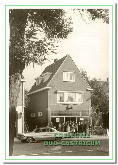 Het in 1937 gebouwde winkelpand van Bernhard Louman, Dorpsstraat 74. De foto zou zijn gemaakt ter gelegenheid van de bruiloft van dochter Hendrika in 1964, vandaar het grote gezelschap voor de winkel en de speciale auto.