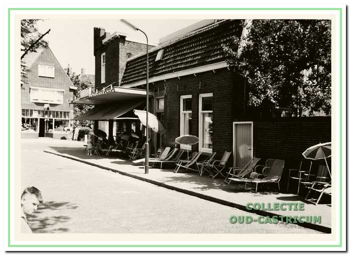 Op de hoek het gedeelte van het pand van Huitenga dat aan Welkers werd verhuurd. Aan de overkant van de Dorpsstraat zien we de winkel van Louman met speelgoed en huishoudelijke artikelen. De tuinstoelen hoorden bij het assortiment van Huitenga.