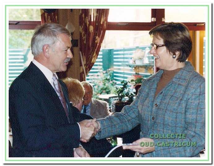 Voorzitter Simon Zuurbier overhandigt het eerste exemplaar van het 25e jaarboekje aan de nieuwe burgemeester A. Emmens - Knol.