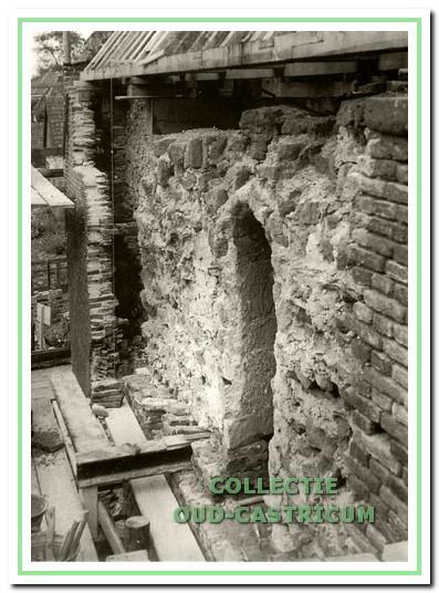 Pancratiuskerk, foto uit 1953: achter een los staande bakstenen muur komt de oude muur van tufsteen te voorschijn met een romaanse vensteropening.