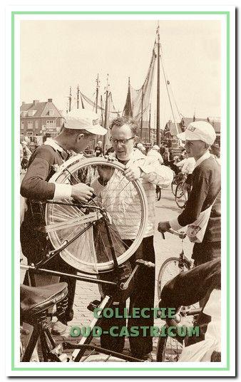 Kapelaan Van der Wel helpt met het plakken van een band in 1958.