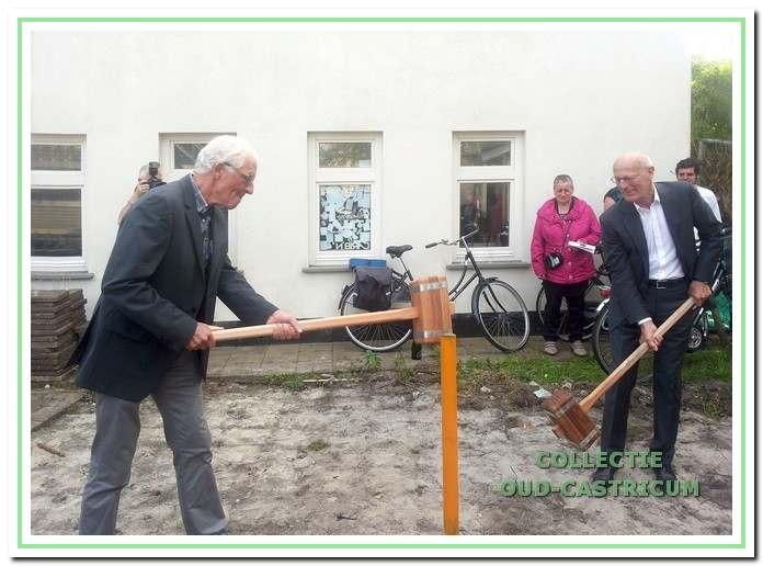 Aad de Wit en Hilbrand Klijnstra slaan de eerste paal voor de nieuwe zaal.
