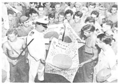 Kapitein Rommel te midden van Amerikaanse militairen die de door hen veroverde Japanse vlaggen tonen.