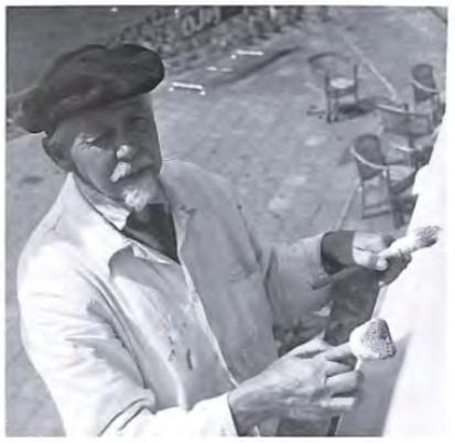 Sijf Portegies bezig met het schilderwerk van de voorgevel van café De Harmonie thans een chinees restaurant aan de Stationsweg.