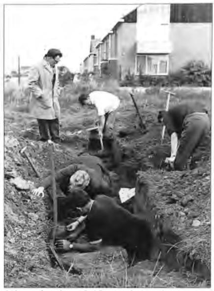 Leden van de werkgroep Oud Castricum bezig met het graven van een proefsleuf; Van Deelen kijkt vanaf de kant toe, naast hem de heer Niek Steeman.