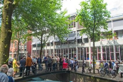 De genodigden wachten op de loopbrug over de Rechtboomssloot bij de Brandewijnsteeg.
