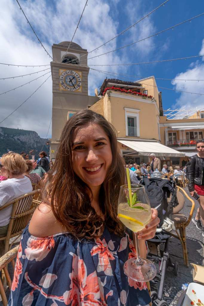 Woman drinking lemon spritz in Piazzetta on a day trip to Capri