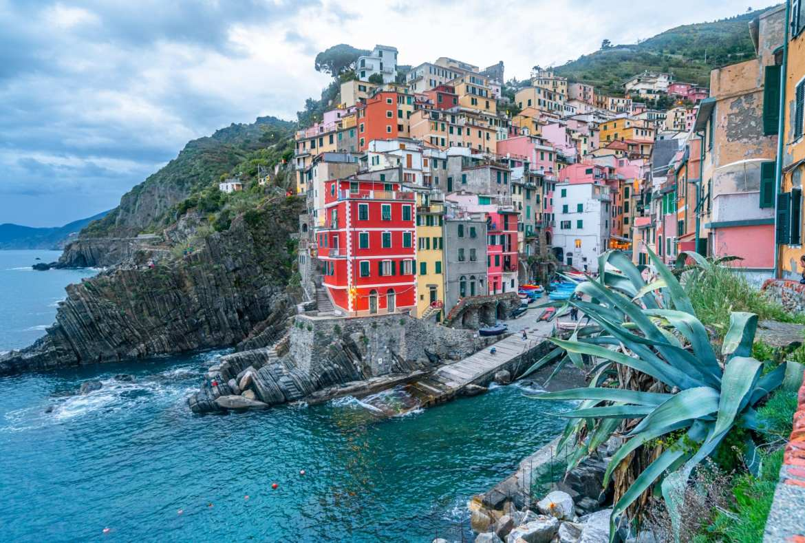 View of Riomaggiore at sunset with the sea in front of it--one of our Cinque Terre tips is to watch at least one sunset in the villages if you can!