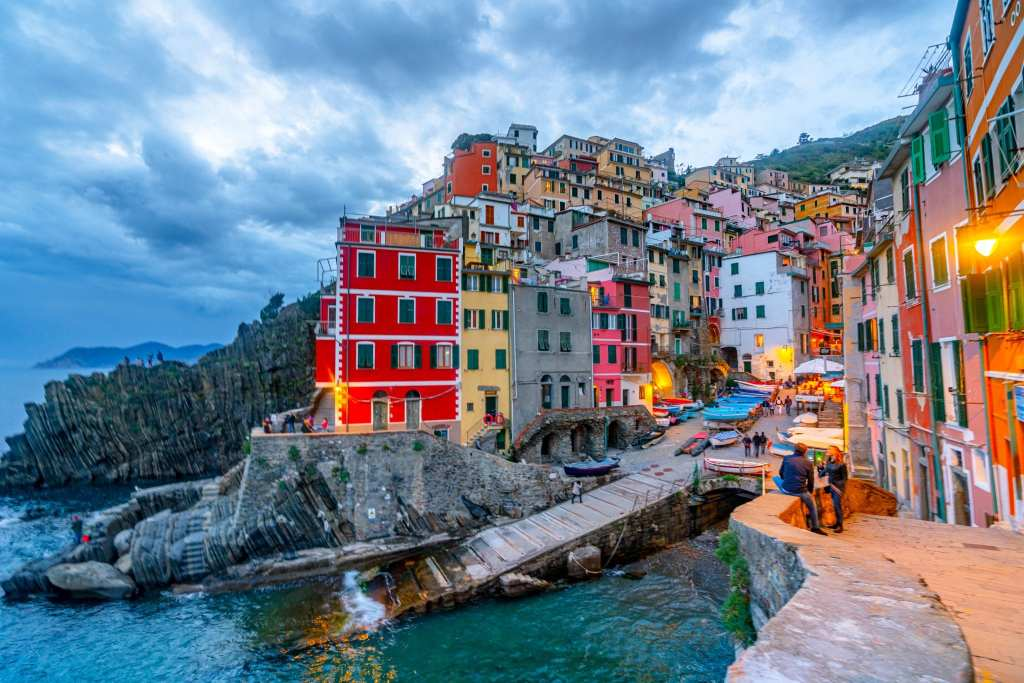 Riomaggiore at night, with lights showing lit up on colorful houses and the sea dark below.