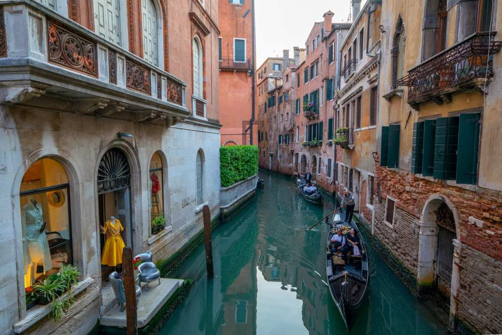 Photo of 2 gondolas in a small canal in Venice.