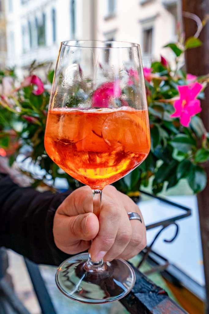 Close up photo of an Aperol Spritz in Venice that is being held in front of pink flowers