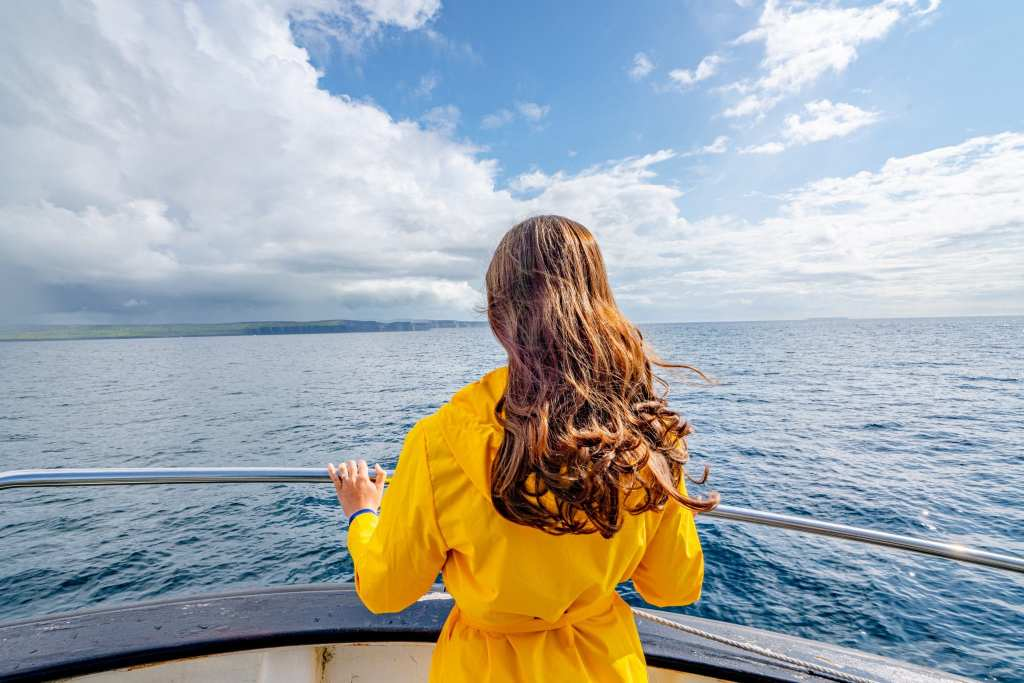 Kate Storm in a yellow raincoat on the ferry from Inisheer to Doolin. You can see the Cliffs of Moher far off in the distance.