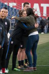Carli Lloyd hugs Hope Solo before Solo is honored for earning 200 caps with the U.S. (Manette Gonzales)