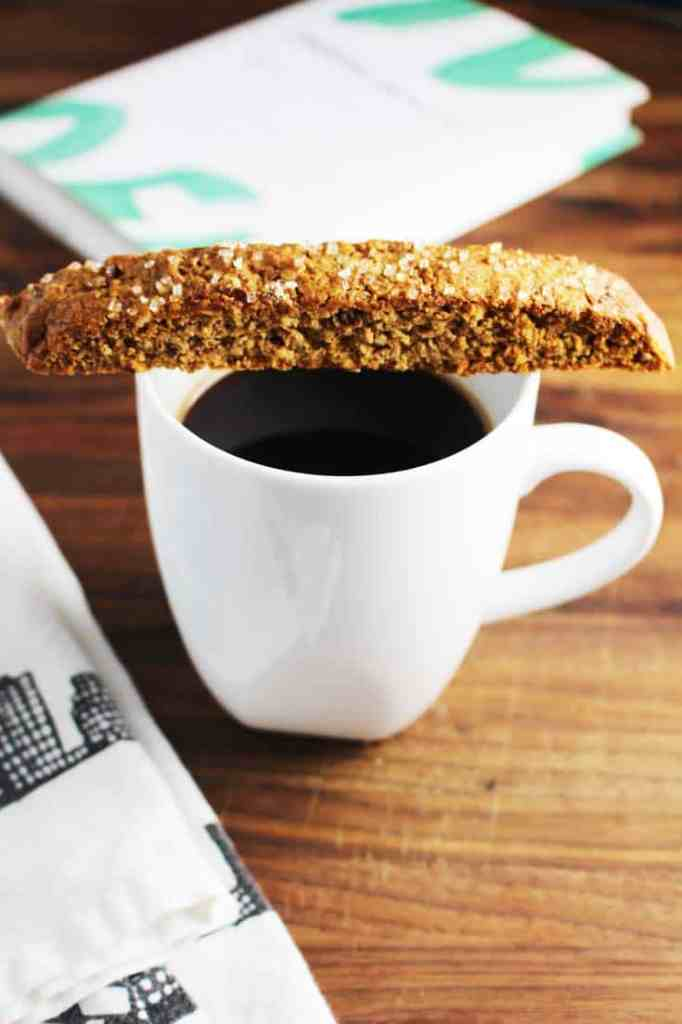 Fig and walnut biscotti laying across the top of a cup of black coffee in a wooden table.
