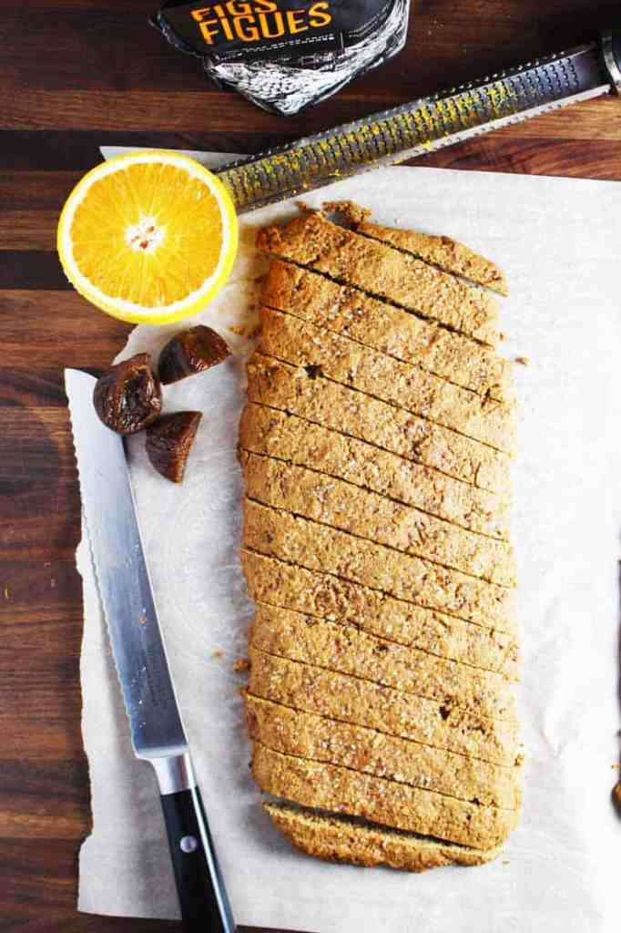 Fig and walnut biscotti, sliced, on a wooden table