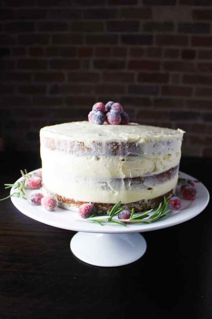 Gingerbread cake with brown butter cream cheese frosting on a cake stand, decorated with sugared cranberries