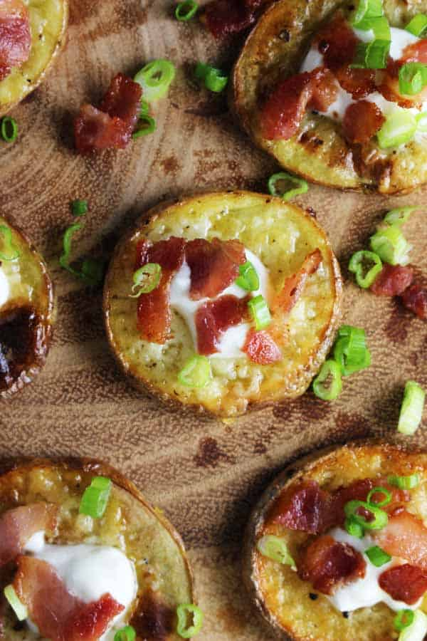 Closeup overhead view of loaded baked potato bites with a dollop of sour cream sprinkled with bacon and chives on a serving platter