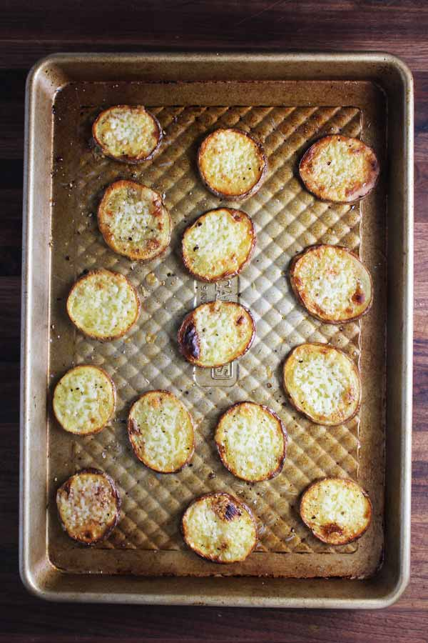 Roasted potato slices with broiled cheese on a baking sheet for loaded baked potato bites