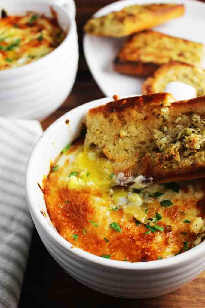 Baked eggs in purgatory in a bowl with a piece of garlic bread
