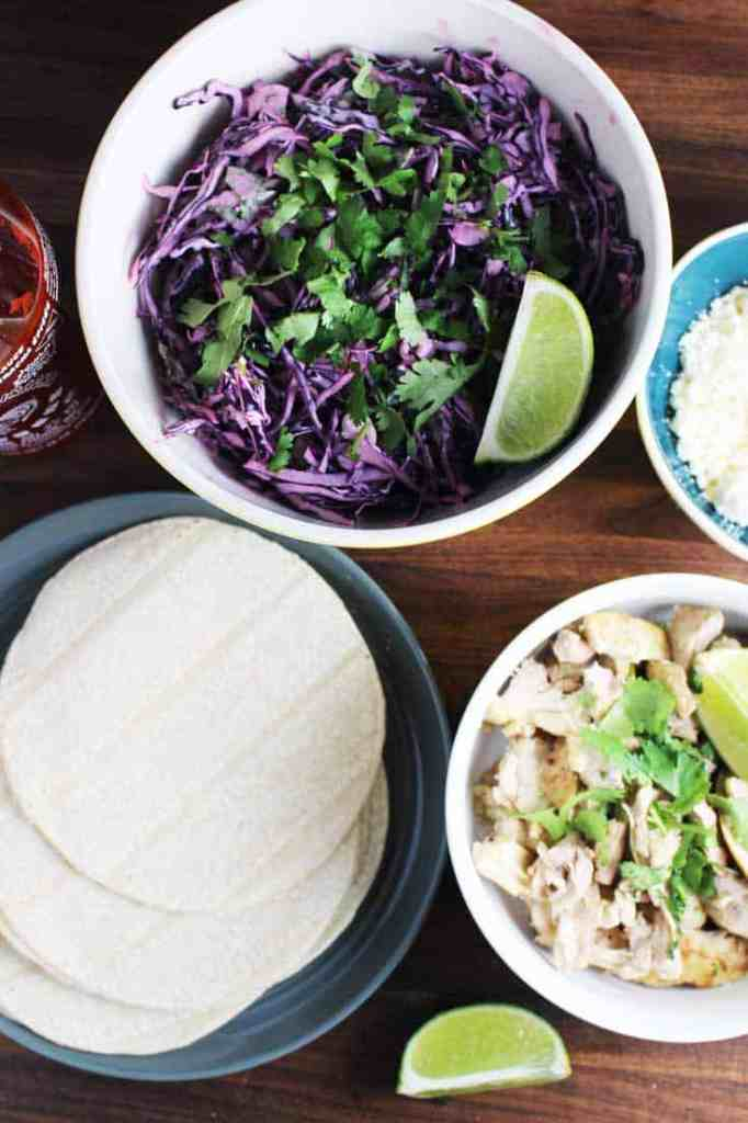 Components of easy chicken taco recipe in bowls. Chicken, cilantro lime slaw, tortillas and cheese