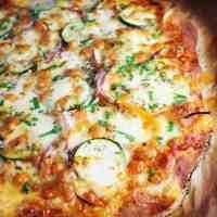 Veggie pizza, unsliced, on parchment paper