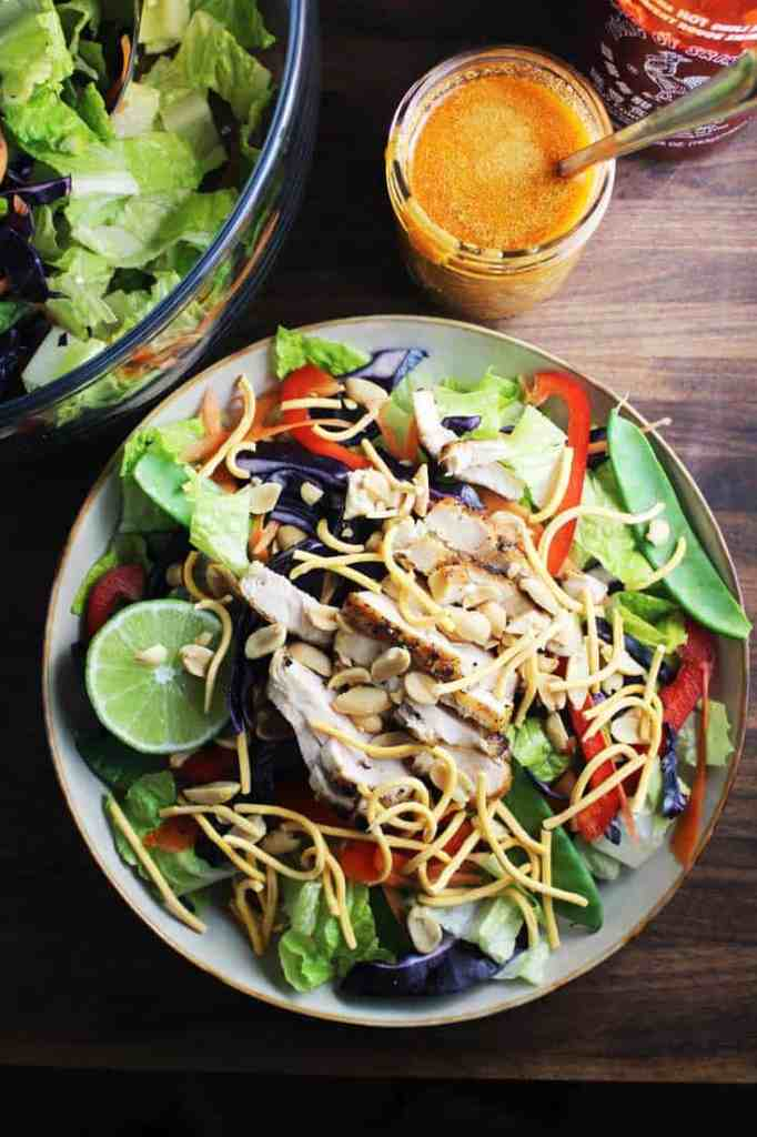 Asian chicken salad tossed in a bowl with peanut sriracha dressing on the side