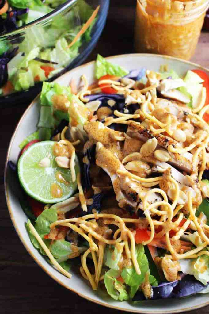 Closeup view of Asian chicken salad tossed with sriracha peanut dressing in a bowl