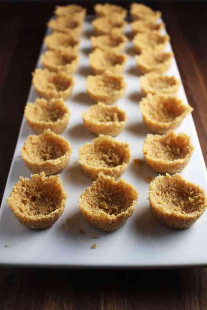 Unfilled graham cracker tart shells for mini cheesecake tarts on a rectangular platter