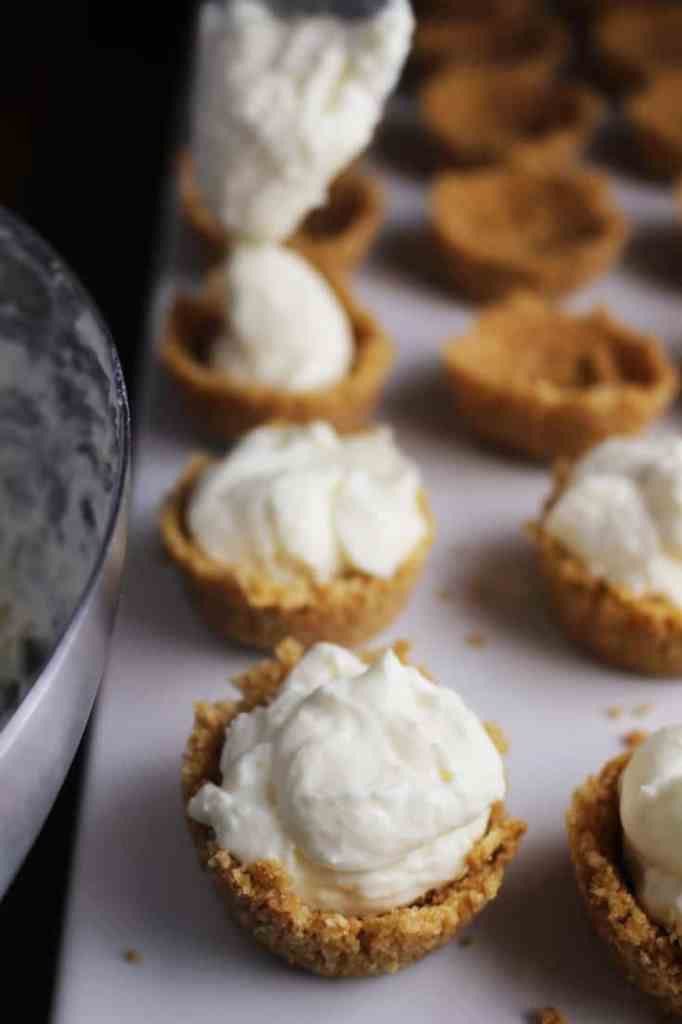 Graham cracher tart shells being filled for mini cheesecake tarts