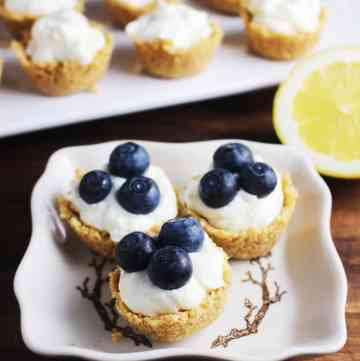 Lemon cheesecake tarts garnished with blueberries on a plate