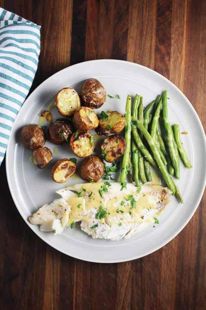 overhead view of a plate of fish, green beans and potatoes from a sheet pan dinner