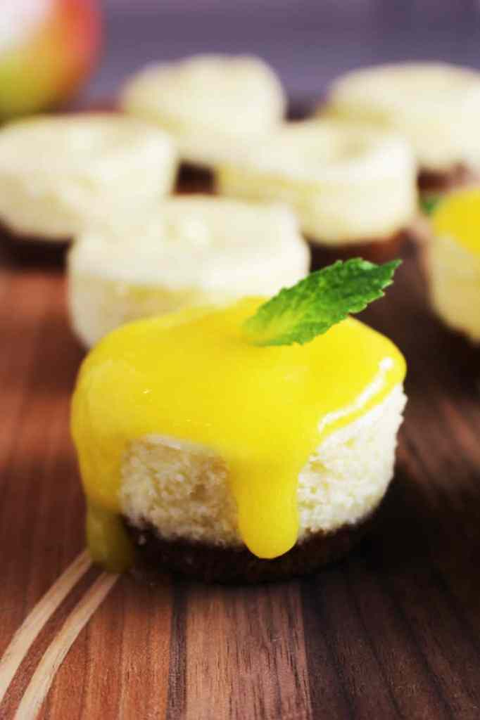 Mini cheesecake topped with mango coulis and a mint leaf