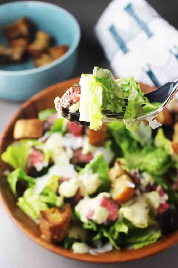 A forkful of caesar salad recipe with steak