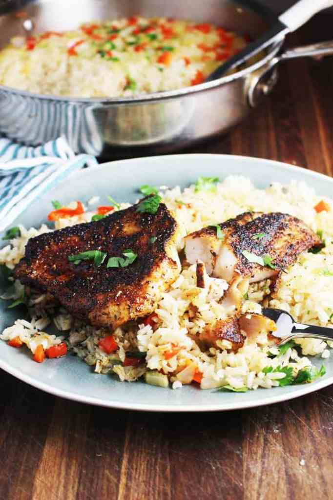 Cajun blackened fish recipe over rice on a plate