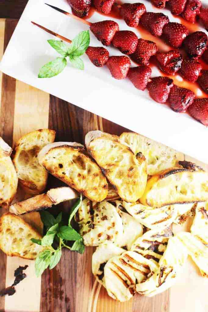 Grilled strawberries on skewers, grilled halloumi and bread on a wooden board