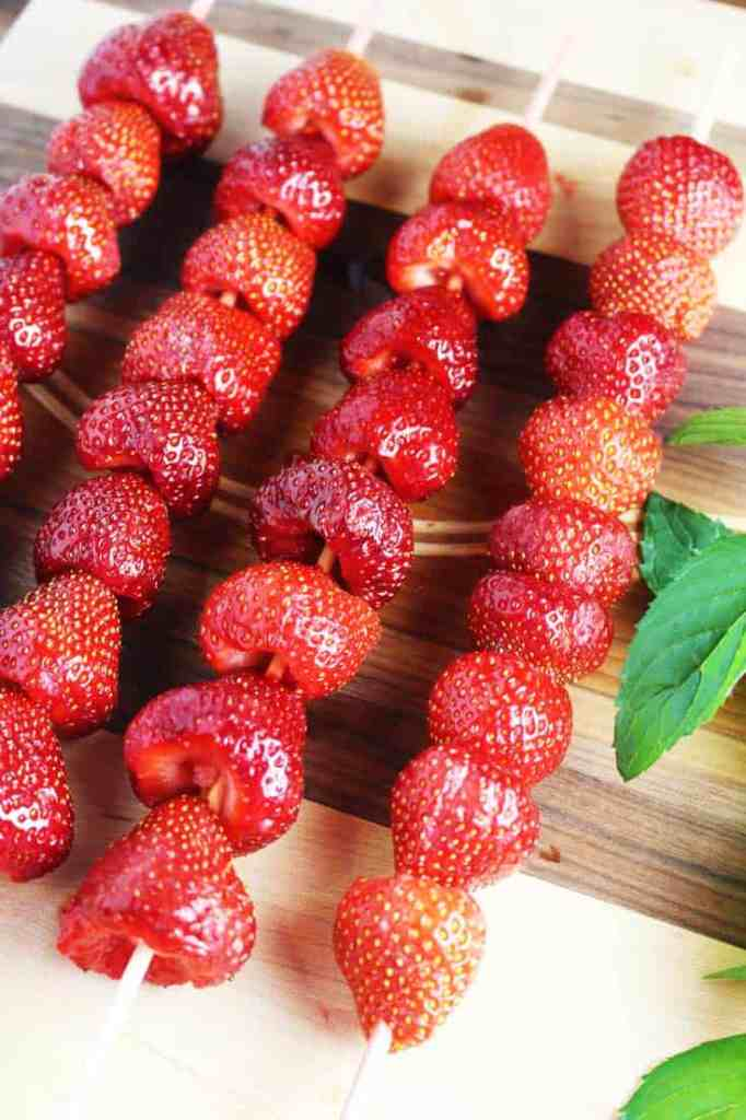 Fresh strawberries on skewers on a wooden board
