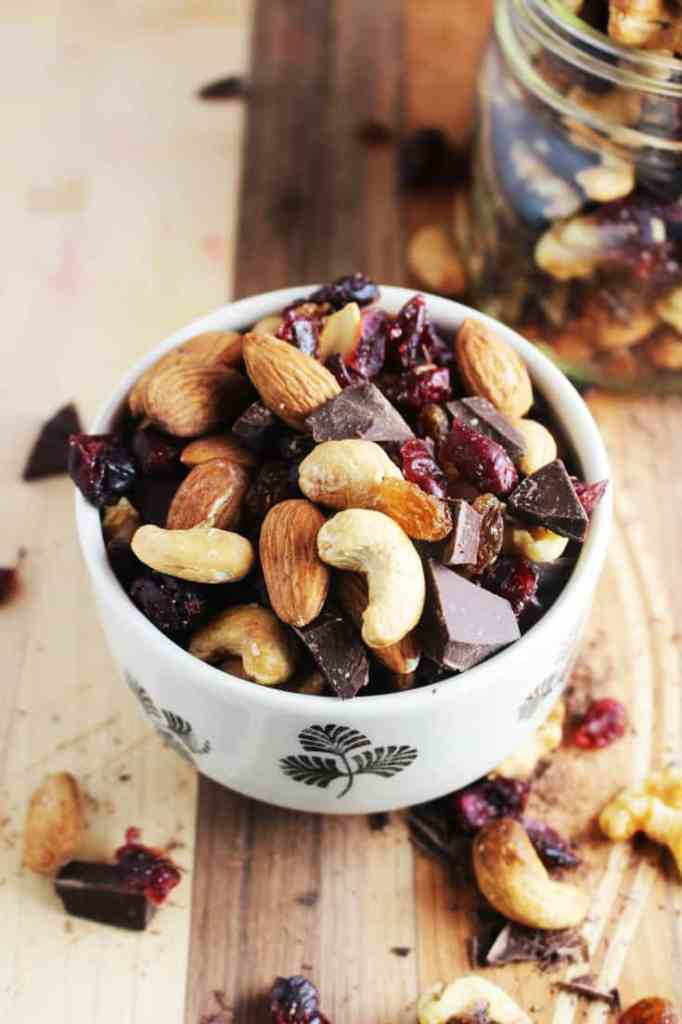 Healthy trail mix in a bowl on a wooden board