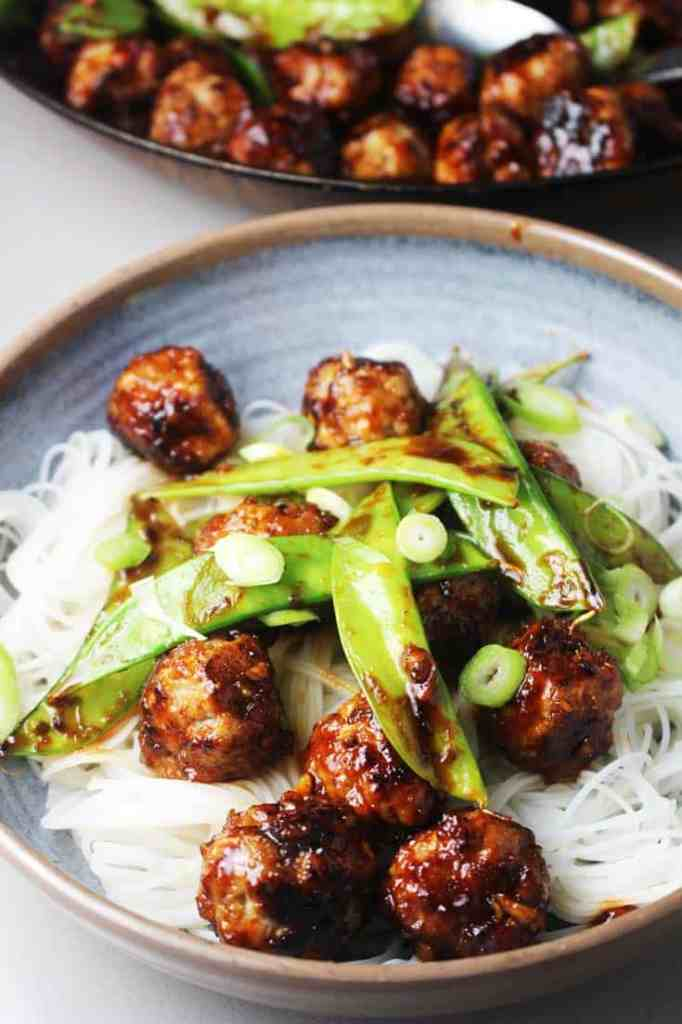 Asian meatballs with honey and sriracha in a bowl over rice noodles and snow peas