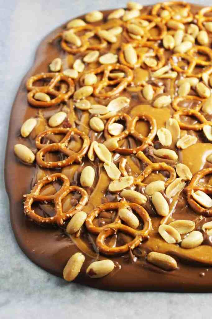 melted chocolate sprinkled with caramel, peanuts and pretzels for sweet and salty chocolate bark