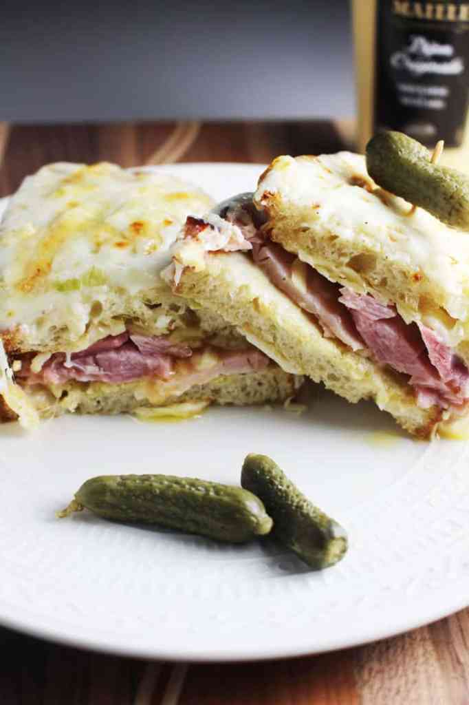Croque monsieur sandwich sliced in half and served on a plate with a gherkin pickle.