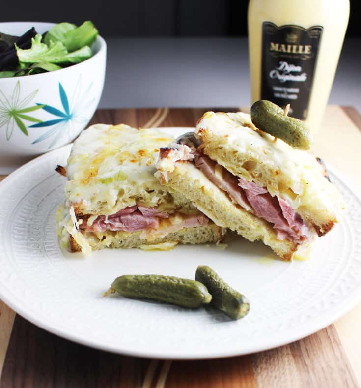 Closeup of a croque monsieur sandwich sliced in half and served on a plate with a gherkin pickle.
