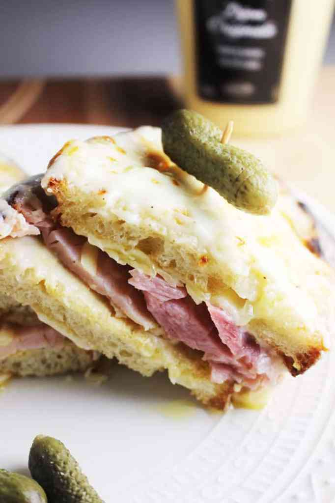 A croque monsieur sandwich sliced in half and served on a plate with a gherkin pickle.