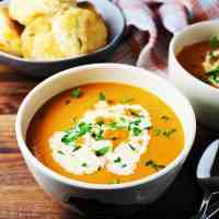 Bowl of tomato soup garnished with cream and parsley, with a bowl of biscuits in the background