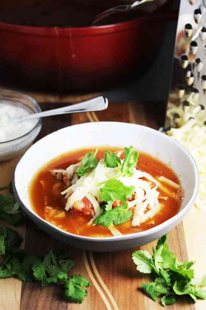 Chicken tortilla soup in a bowl topped with tortilla chips, cheese, sour cream and cilantro