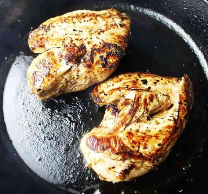 Greek marinated chicken breasts cooked in a cast iron pan