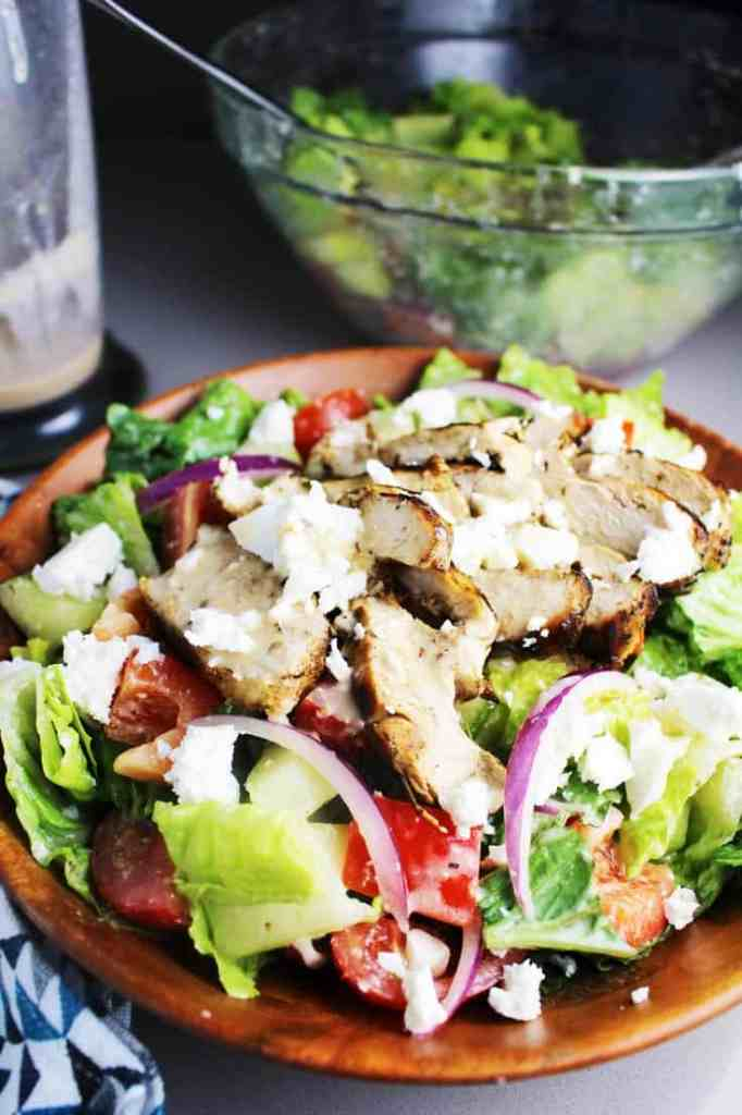 Tossed green Greek chicken salad in a wooden bowl