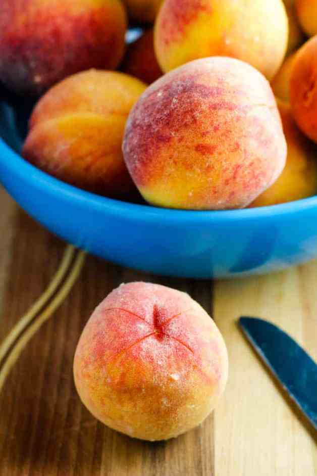 A bowl of peaches, one with an x cut into it for removing the peel