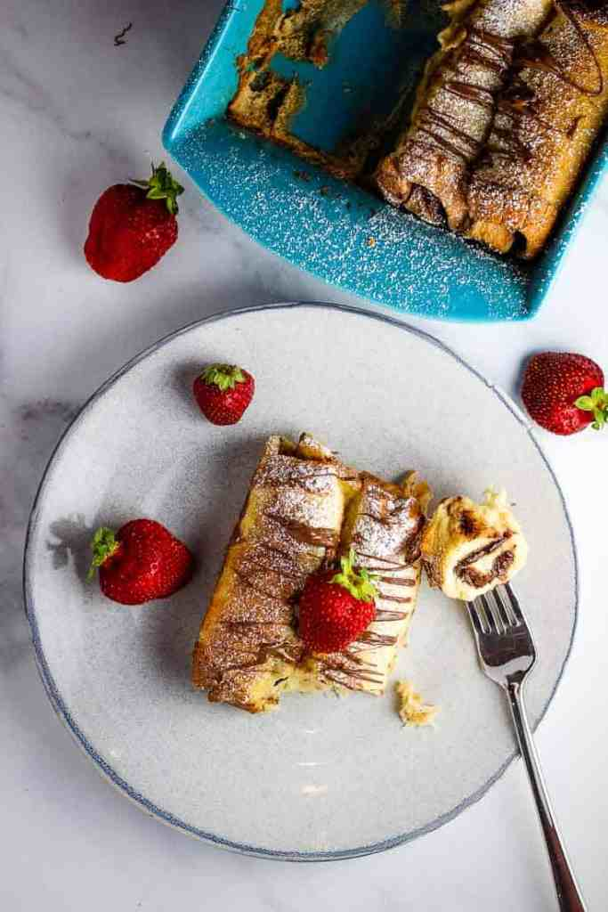 Overhead view of Nutella French toast casserole in the pan and with a serving on a plate