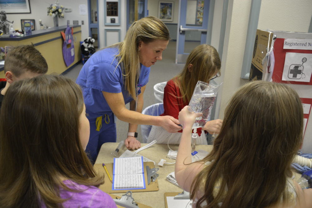 nurse with IV bag and students