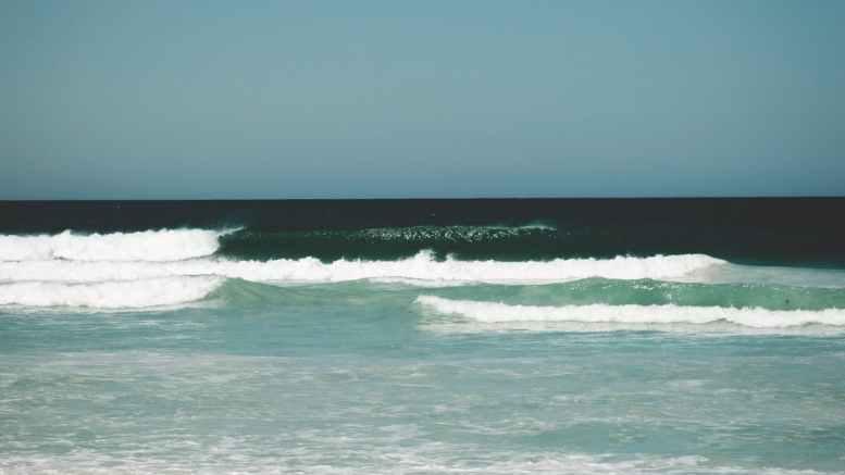 foamy waves of ocean washing sandy coast